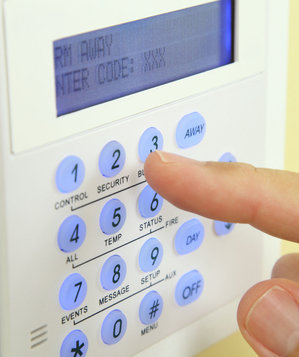 Person entering code on alarm system keypad