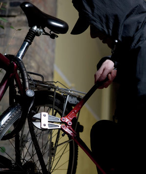 Man in black hoodie cutting bicycle lock with bolt cutters