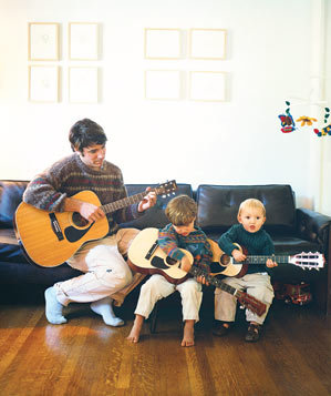 A dad with small boys playing guitar