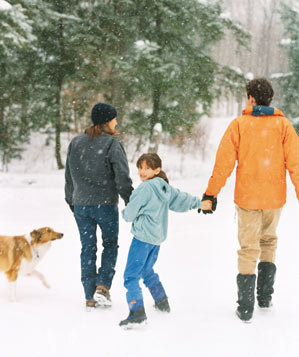 Family with a dog playing in the snow