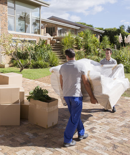 Movers carrying boxes into house