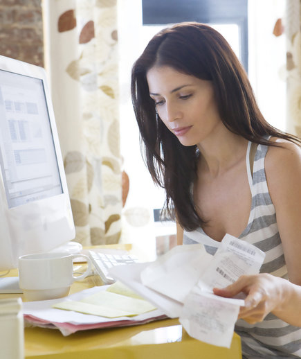 Woman keeping track of receipts with laptop