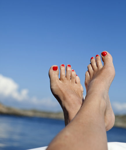 Woman's feet against blue sky