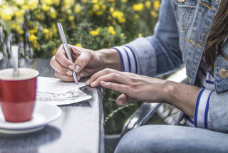 woman-writing-letter-cafe