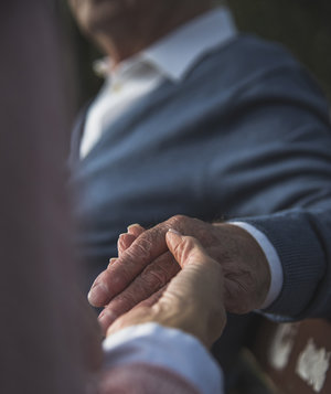 woman-holds-elderly-fathers-hand