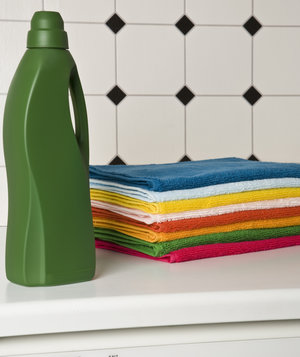 colorful-towels-and-green-detergent-bottle-on-top-of-washer