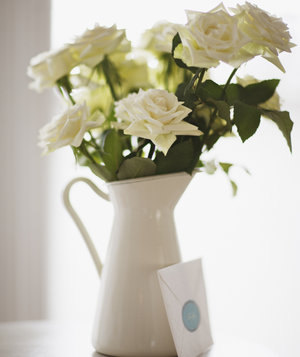 card-leaning-against-white-rose-bouquet-in-pitcher