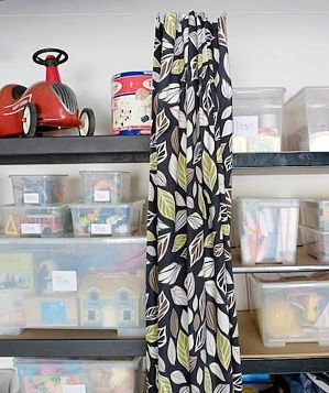 Hang Wire And Curtain Panels To Prettily Hide Storage Bins