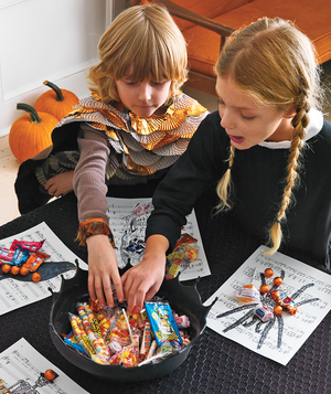 children-reaching-into-a-bowl-of-candy-at-a-halloween-party