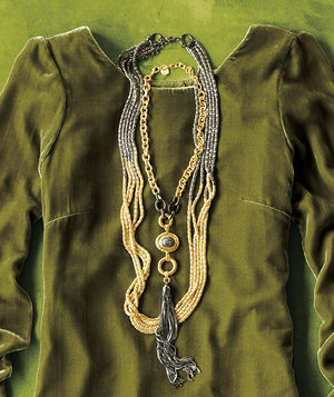 silver-and-gold-statement-necklace-against-green-monochromatic-background