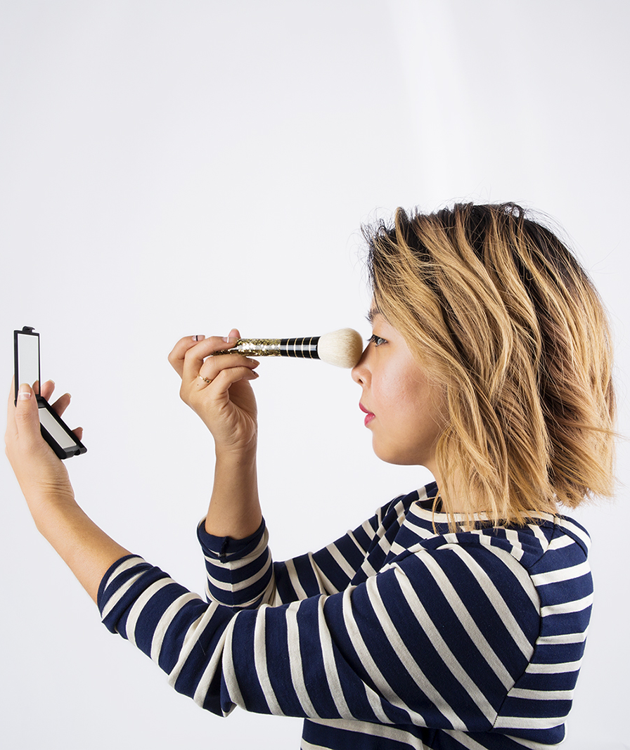 girl-applying-eye-makeup-and-looking-into-handheld-mirror