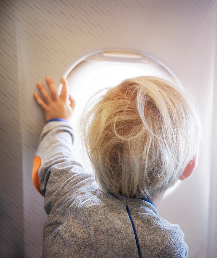 boy-looking-out-airplane-window