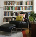 room-built-in-white-bookshelf-black-leather-armchair