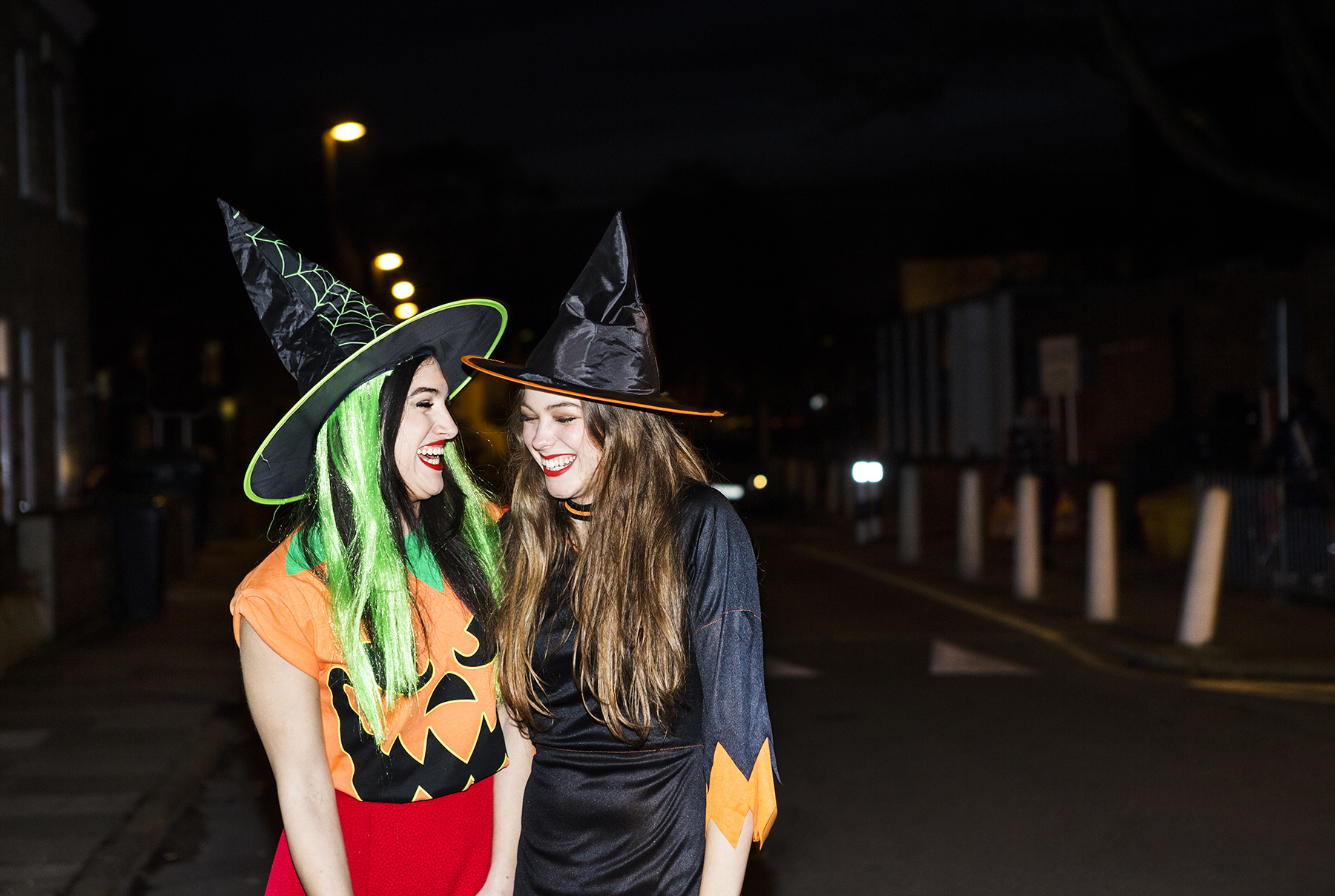 2 young women dressed as witches, laughing